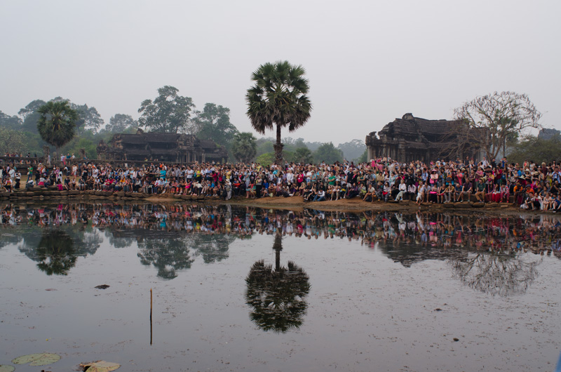 Crowds of tourists waiting for the sun to rise over Angkor Wat