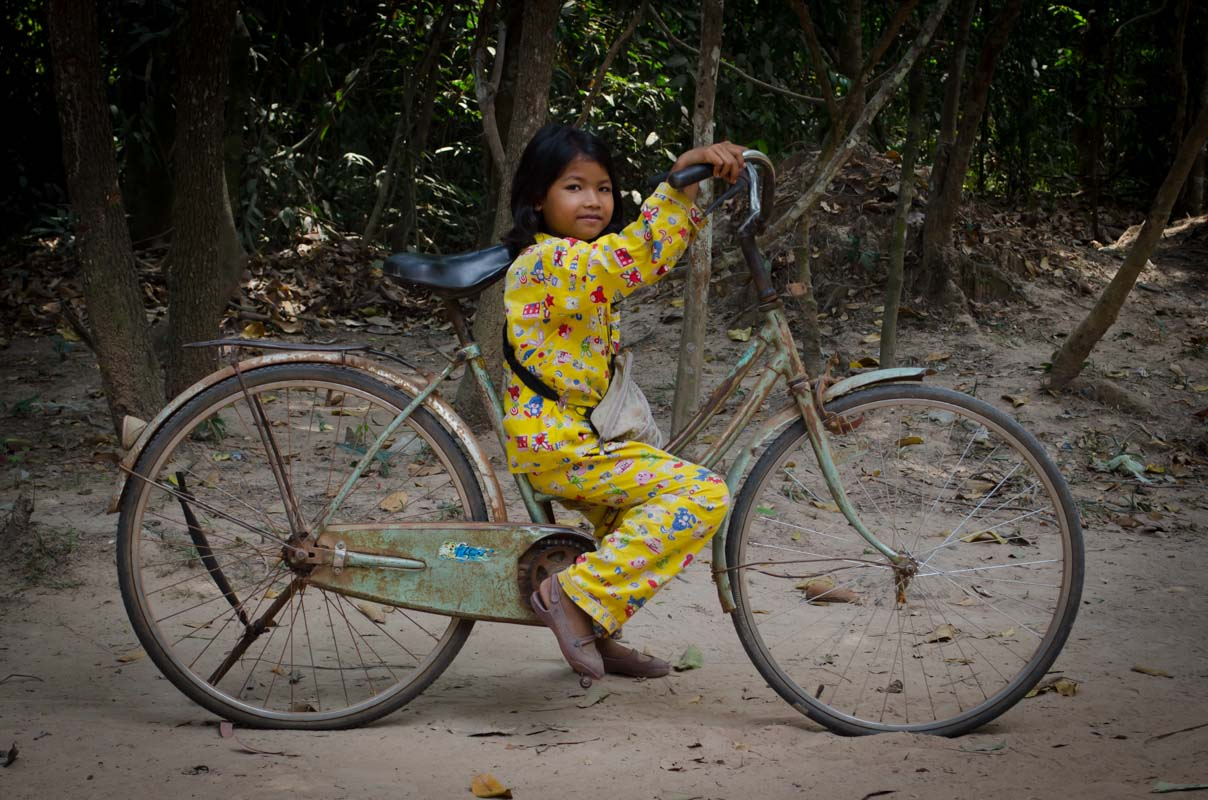 Girl in yellow pajamas on bicycle