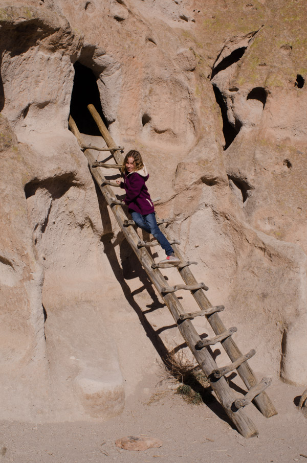 Sydney on a ladder at Bandelier National Monument